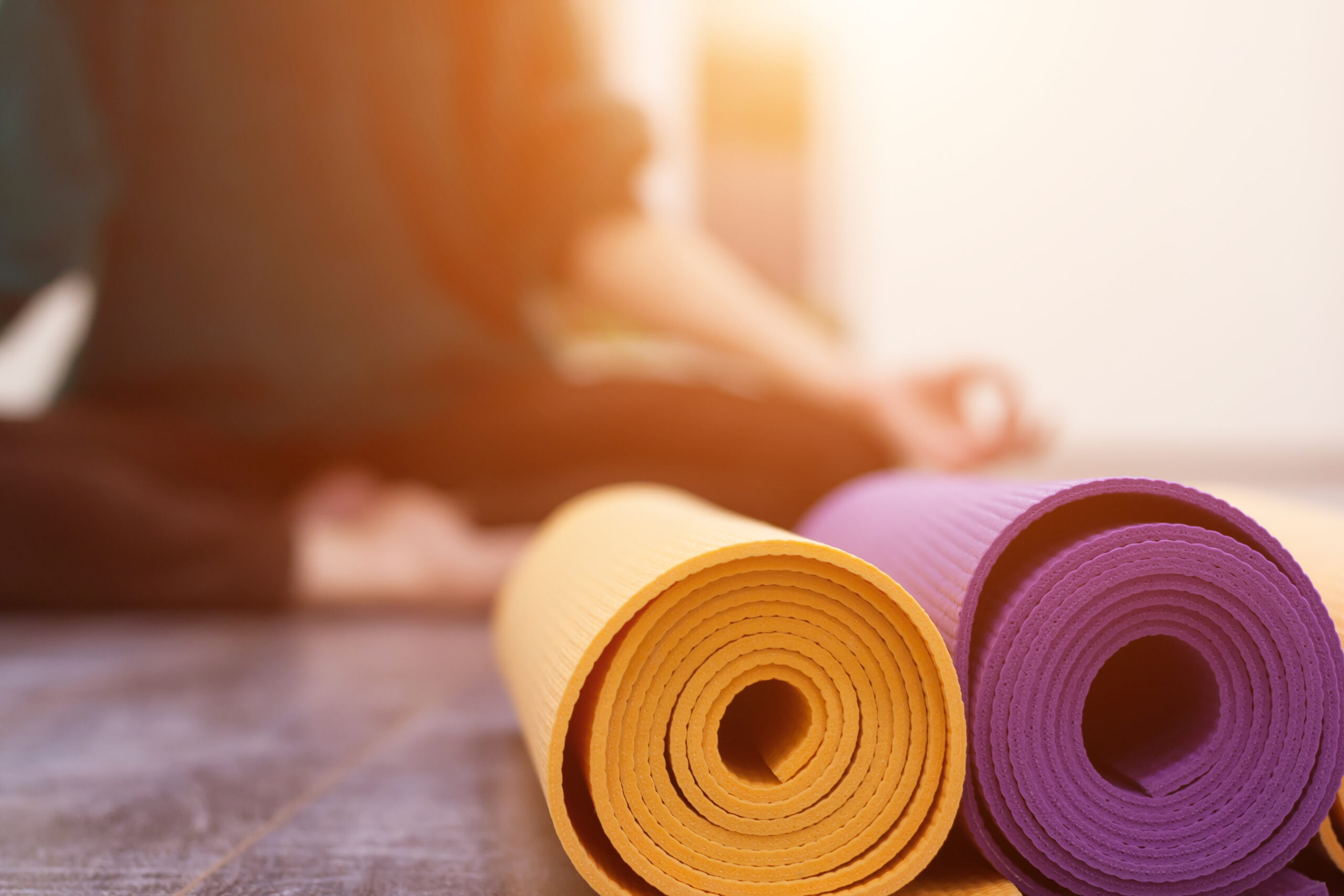 Closeup view of yoga mat and woman sitting in lotus pose on background. Yoga exercising in gym